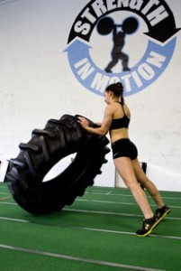Tracy flipping a tire courtesy of JTS Strength