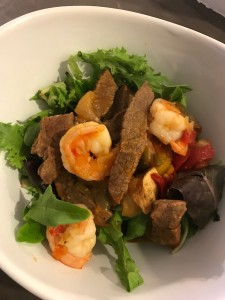 Steak and shrimp over a bed of mixed greens. I topped this meal with an organic, Whole30 approved salsa.
