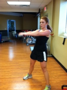 Cammy finishes the swing by using her hips to propel the motion of the bell forward and momentum carries the bell to shoulder height.