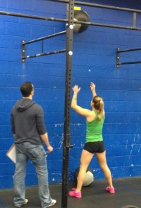 Ali tosses to the target on the wall.