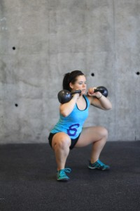Squatting with double kettlebells.